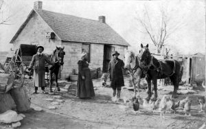 John Summer and his family standing in front of their home located two miles northeast of Dunlap, Kansas.