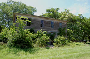 Overgrown building in Neal, Kansas by Kathy Weiser-Alexander.